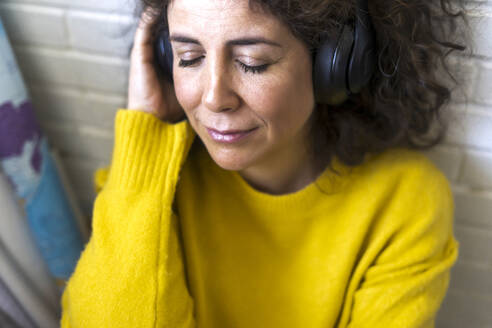Portrait of woman with closed eyes listening to music with headphones - ERRF03806