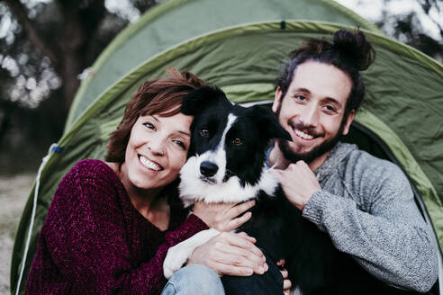 Portrait of happy couple with dog at a tent - EBBF00054