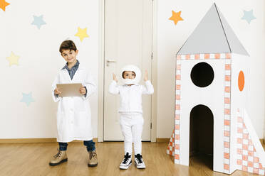 Siblings playing astronaut and researcher at rocket - JRFF04458