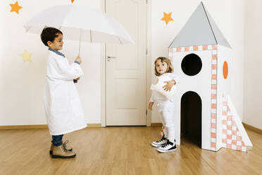 Siblings playing astronaut and researcher with umbrella at rocket - JRFF04461
