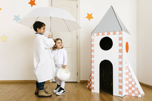 Siblings playing astronaut and researcher with umbrella at rocket - JRFF04464
