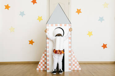 Girl wearing costume and playing astronaut looking into rocket - JRFF04473