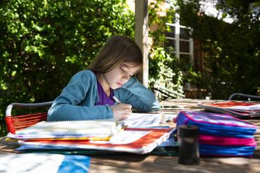 Girl sitting at garden table doing homework - LVF08892