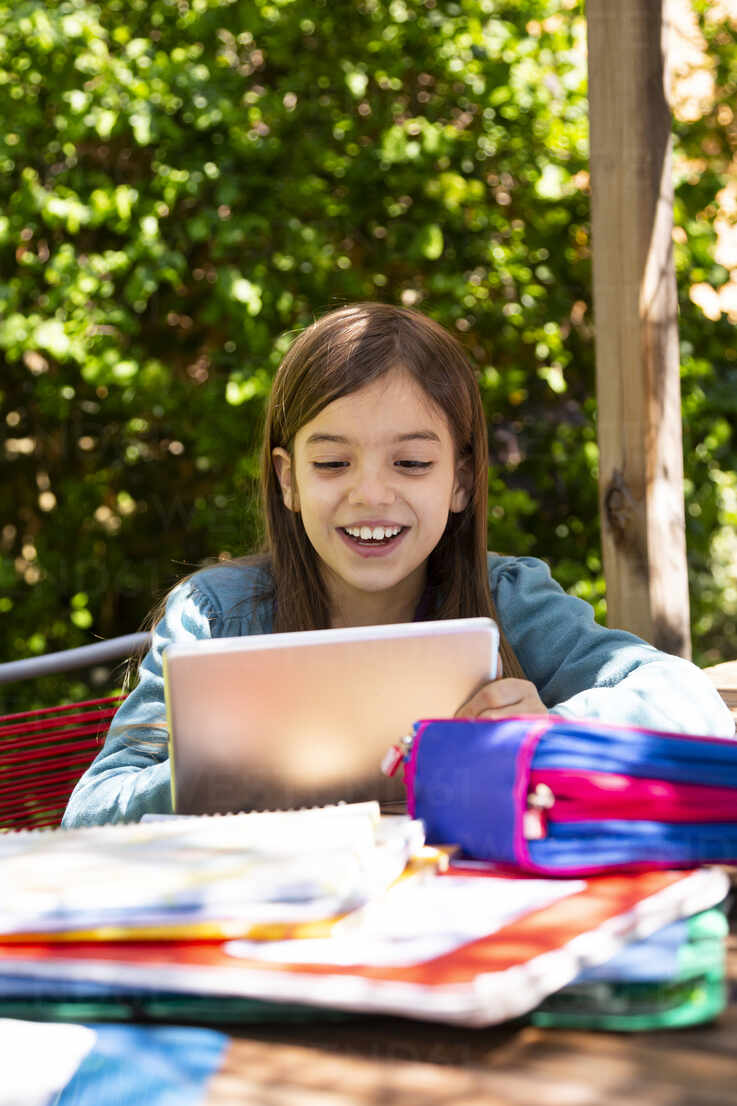 Girl sitting at garden table doing homework and using tablet - LVF08895 - Larissa Veronesi/Westend61