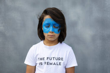 Portrait of boy with painted blue mask on his face wearing t-shirt with imprint 'The Future is Female' - VABF02931