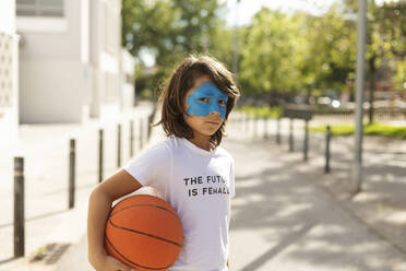 Portrait of boy with painted blue mask on his face holding basketball - VABF02937