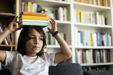 Portrait of boy balancing stack of books on his head - VABF02946