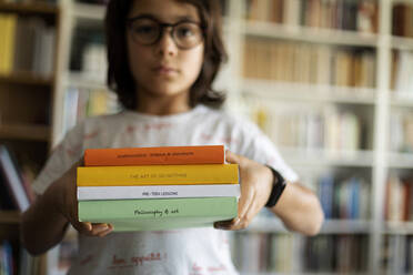Boy holding stack of four books - VABF02949