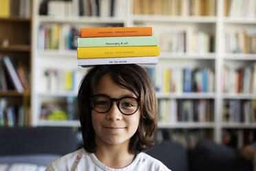 Portrait of smiling boy balancing stack of books on his head - VABF02952