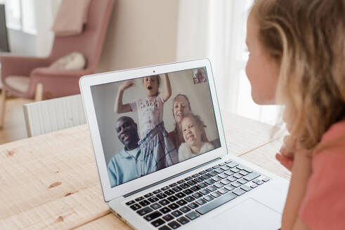 Girl having a video call with her family at home - CAVF81218