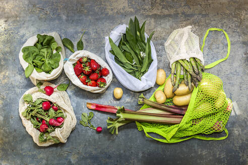 Studio shot of mesh bags with various fruits and vegetables - STBF00543