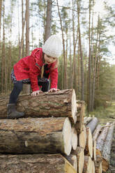 Little girl climbing on stack of wood in the forest - BRF01461
