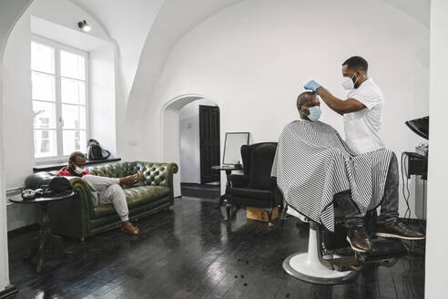 Barber wearing surgical mask and reusable gloves cutting hair of the customer - AHSF02534