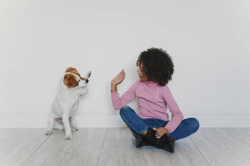 Little girl sitting on the floor playing with her dog - EBBF00075