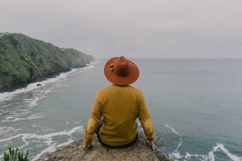 Rear view of man sitting on a rock at the coast on Sao Miguel Island, Azores, Portugal - AFVF06305