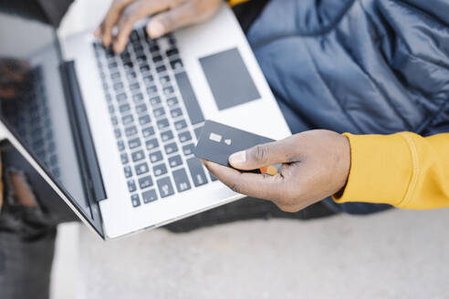 Close-up of man using laptop and credit card for online shopping - JCZF00083