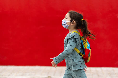 Girl walking with backpack and mask along red wall - EGAF00112