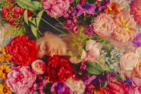 Beautiful woman sleeping under glass pane with flowers - ERRF03815