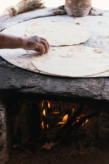 Side view of fresh tortilla cooking on an open fire comal - CAVF81691