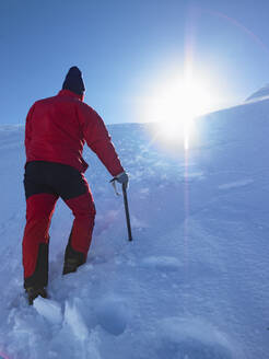 Man hiking up snowy hill towards a summit - CAVF81906