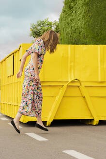 Woman in flower dress, jumping in the street in front of yellow container - ERRF03829