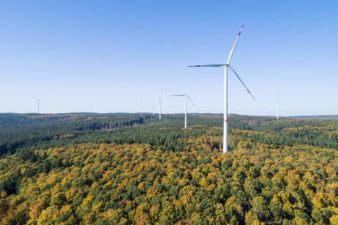 Germany, Baden-Wurttemberg, Drone view of clear sky over wind farm in autumn forest of Swabian Jura - RUEF02926