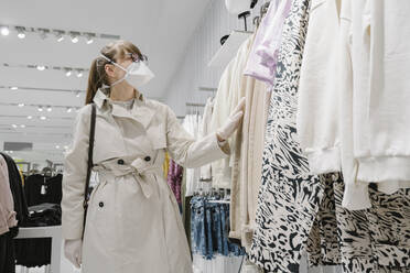 Woman with face mask and disposable gloves shopping in a fashion store - AHSF02590