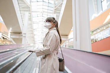 Woman with face mask and disposable gloves on an escalator in a shopping center - AHSF02593