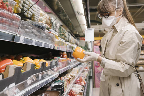Woman with face mask and disposable gloves in a supermarket - AHSF02599