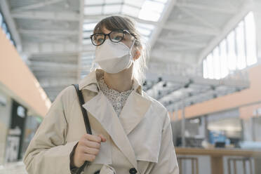 Portrait of woman wearing face mask in a shopping center - AHSF02602