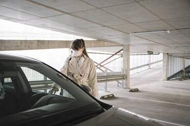 Woman wearing face mask opening car in a car park - AHSF02605