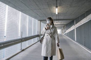 Woman wearing face mask walking in corridor of a car park after shopping - AHSF02608
