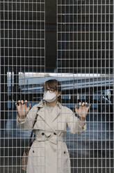 Woman wearing face mask standing behind grating in a car park - AHSF02611