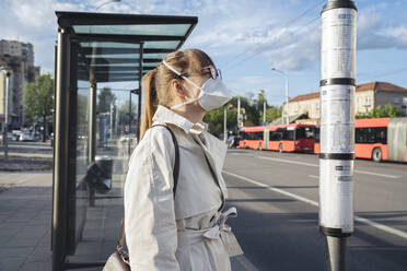 Woman wearing face mask checking schedule of public transport in the city - AHSF02614