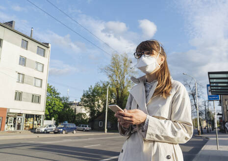 Woman wearing face mask and holding smartphone waiting for a public transport in the city - AHSF02617