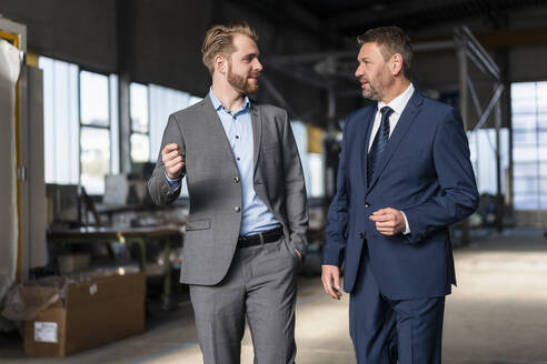 Two businessmen walking and talking in a factory - DIGF10989