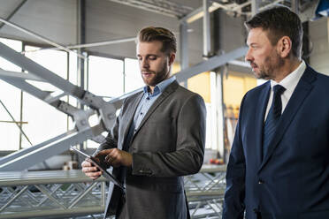 Two businessmen with tablet having a meeting in a factory - DIGF11061