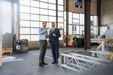Two businessmen having a meeting in a factory - DIGF11076