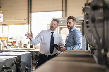 Two businessmen with tablet having a meeting in a factory - DIGF11085