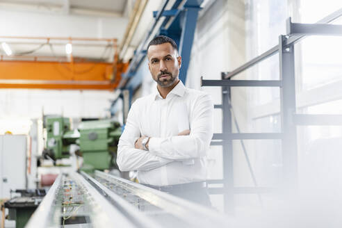 Businessman standing at metal rod in factory hall - DIGF11170