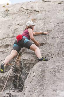 Young woman climbing rock - FVSF00302