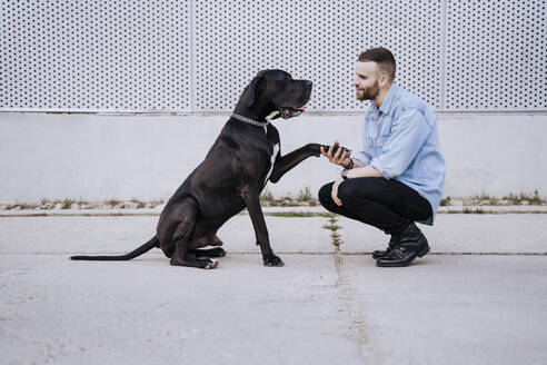 Young man teaching his dog outdoors - EBBF00117
