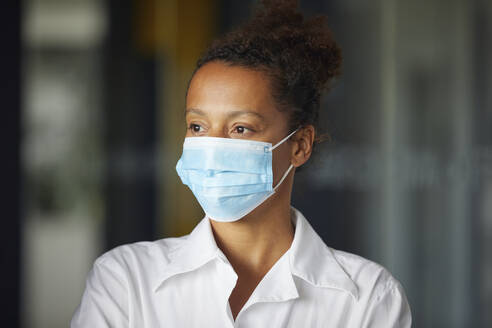 Portrait of businesswoman wearing light blue protective mask looking at distance - RBF07688