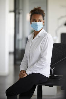 Portrait of businesswoman wearing light blue protective mask - RBF07691