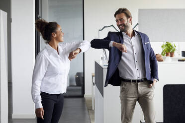 Colleagues greeting each other in office during Corona crisis - RBF07703