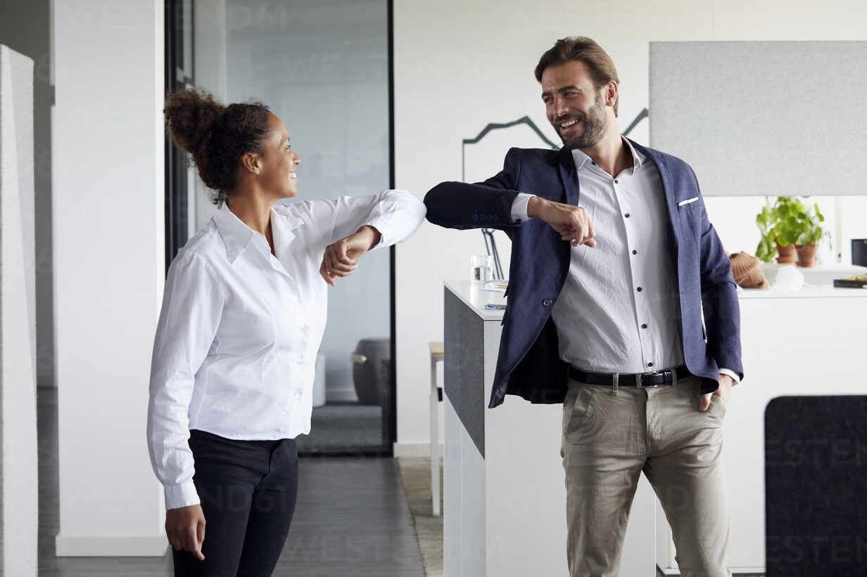 Colleagues greeting each other in office during Corona crisis - RBF07703 - Rainer Berg/Westend61