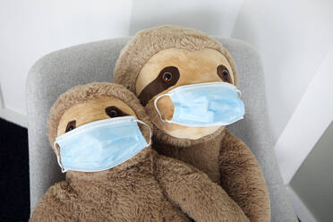 Two soft toys on arm chair with protective masks - RBF07709