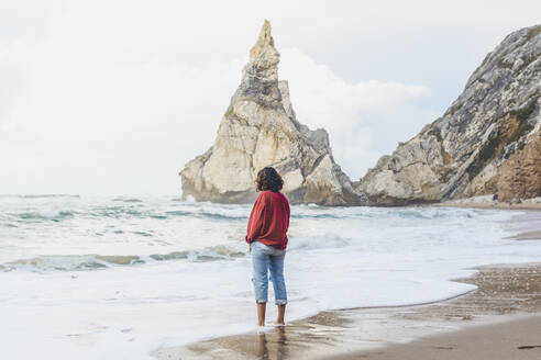 Young woman standing on shore at Praia da Ursa, Lisboa, Portugal - FVSF00341