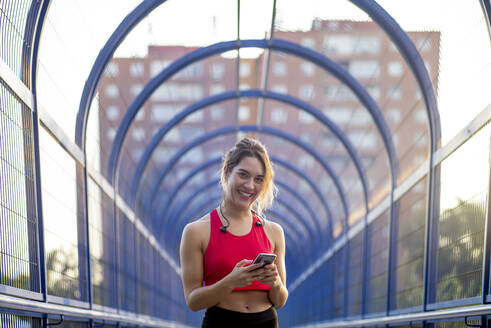 Smiling confident female athlete using smart phone while standing on covered bridge in city - OCMF01250