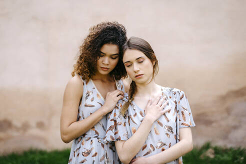 Loving sisters with eyes closed embracing while standing against old wall - TCEF00670